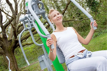 fitness   mature woman - Mature woman using exercise machine in park Stock Photo - Premium Royalty-Free, Code: 649-07710283