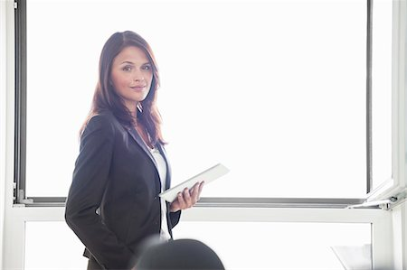 presentation (displaying) - Mid adult woman holding digital tablet, portrait Stock Photo - Premium Royalty-Free, Code: 649-07710383
