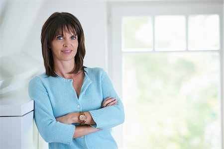 Businesswoman standing in office interior, arms folded Stock Photo - Premium Royalty-Free, Code: 649-07710425