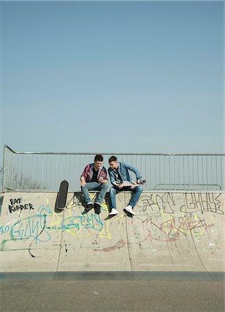 Young men in skatepark, using smartphone Stock Photo - Premium Royalty-Free, Code: 649-07710450