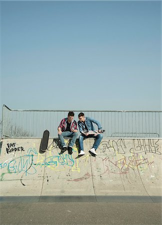 Young men in skatepark, using smartphone Stock Photo - Premium Royalty-Free, Code: 649-07710450