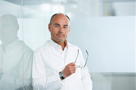 doctors - Male doctor leaning against reflective wall Stock Photo - Premium Royalty-Free, Code: 649-07710463