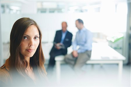 Woman posing for camera, businessmen in background Stock Photo - Premium Royalty-Free, Code: 649-07710473