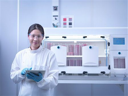 Portrait of scientist with bacterial cultures inside laboratory workstation Stock Photo - Premium Royalty-Free, Code: 649-07710511