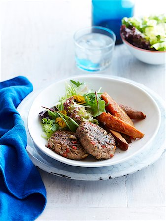 Still life of turkey patties with sweet potato and mesclun salad Stock Photo - Premium Royalty-Free, Code: 649-07710549