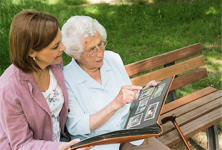 Senior woman sitting on park bench with granddaughter, looking at old photograph album Stock Photo - Premium Royalty-Free, Code: 649-07710569