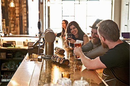 Friends drinking beer at hipster bar Stock Photo - Premium Royalty-Free, Code: 649-07710592