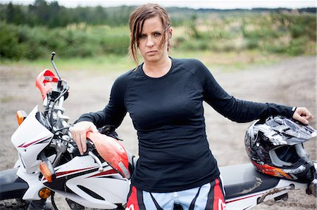 female - Portrait of young adult female motorcyclist leaning on motorcycle Stock Photo - Premium Royalty-Free, Code: 649-07710604