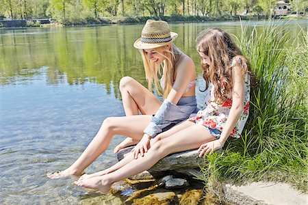Two friends sitting on rocks by water Stock Photo - Premium Royalty-Free, Code: 649-07710614