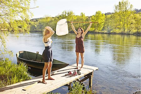 Young women standing on jetty, one holding fishing net Stock Photo - Premium Royalty-Free, Code: 649-07710632