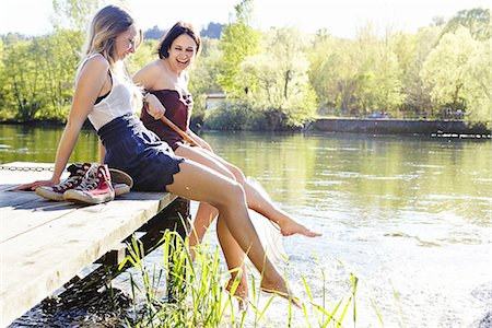 Young women sitting on jetty Stock Photo - Premium Royalty-Free, Code: 649-07710633