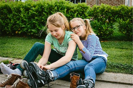 preteen girl pigtails - Two sisters sitting on sidewalk putting on rollerblades Stock Photo - Premium Royalty-Free, Code: 649-07710666