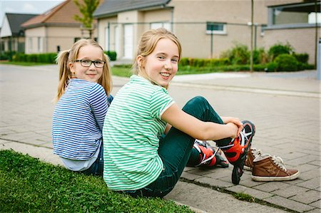 preteen girl pigtails - Portrait of nine year old girl and sister putting on rollerblades on sidewalk Stock Photo - Premium Royalty-Free, Code: 649-07710667