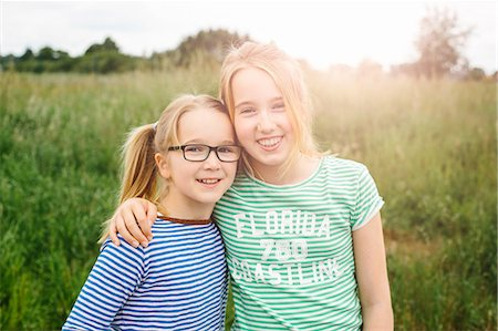 Portrait of eleven year old girl hugging sister in field Stock Photo - Premium Royalty-Free, Code: 649-07710668