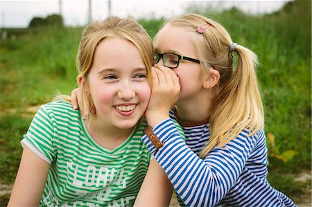 preteen girl pigtails - Nine year old girl whispering to sister in field Stock Photo - Premium Royalty-Free, Code: 649-07710660