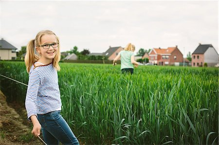 preteen girl pigtails - Portrait of sisters in field, one running and one posing Stock Photo - Premium Royalty-Free, Code: 649-07710661