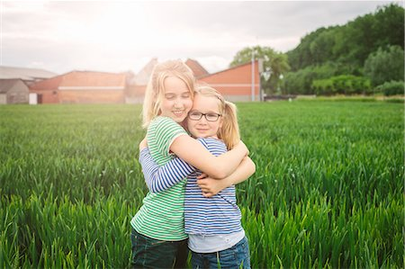 preteen girl pigtails - Portrait of nine year old girl and sister hugging in field Stock Photo - Premium Royalty-Free, Code: 649-07710662