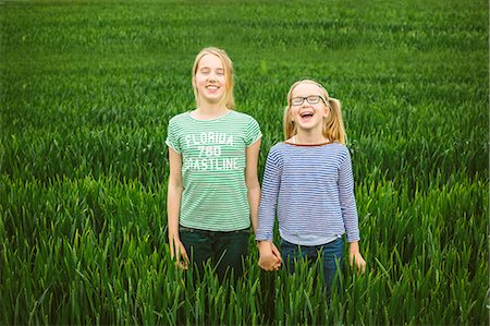 preteen girl pigtails - Portrait of nine year old girl and sister holding hands in field Stock Photo - Premium Royalty-Free, Code: 649-07710663