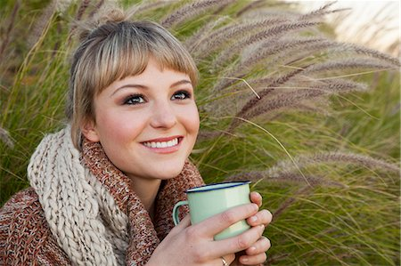 Portrait of young woman amongst long grass with drinks mug Stock Photo - Premium Royalty-Free, Code: 649-07710671