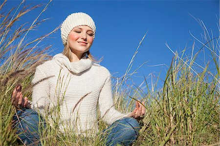 Young woman in yoga lotus position in long grass Stock Photo - Premium Royalty-Free, Code: 649-07710691