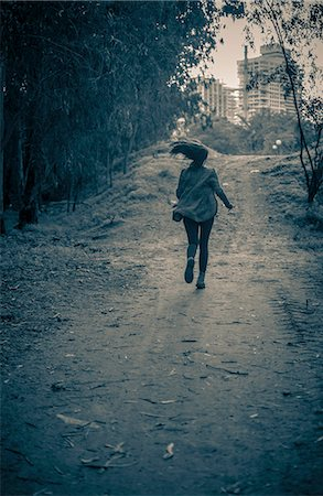running away scared - Young woman running from danger up dirt track toward apartment blocks Stock Photo - Premium Royalty-Free, Code: 649-07710712