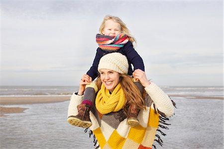 Mid adult woman shoulder carrying daughter on beach, Bloemendaal aan Zee, Netherlands Stock Photo - Premium Royalty-Free, Code: 649-07710725