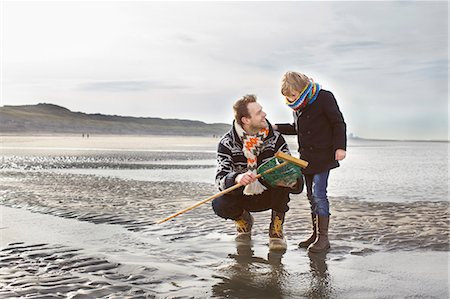 Mid adult man and son with fishing net on beach, Bloemendaal aan Zee, Netherlands Stock Photo - Premium Royalty-Free, Code: 649-07710720