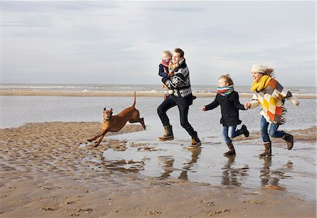 dog and woman and love - Mid adult parents with son, daughter and dog running on beach, Bloemendaal aan Zee, Netherlands Stock Photo - Premium Royalty-Free, Code: 649-07710722