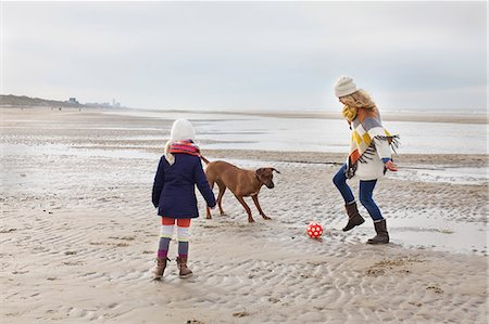 Mid adult woman with daughter and dog playing football on beach, Bloemendaal aan Zee, Netherlands Stock Photo - Premium Royalty-Free, Code: 649-07710739