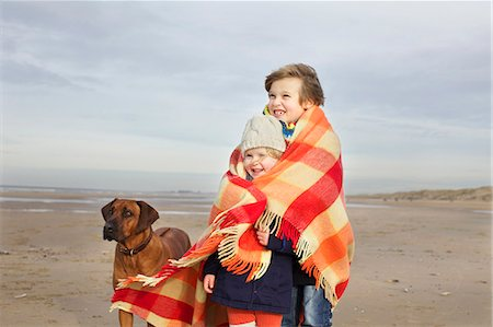 Portrait of three year old girl and brother wrapped in blanket on beach, Bloemendaal aan Zee, Netherlands Stock Photo - Premium Royalty-Free, Code: 649-07710730