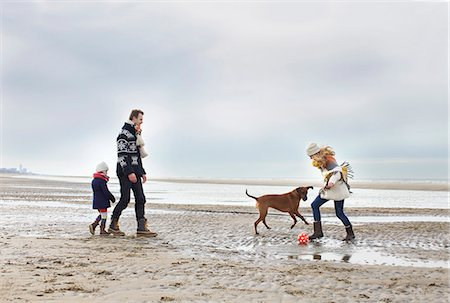 Mid adult parents with daughter and dog playing football on beach, Bloemendaal aan Zee, Netherlands Stock Photo - Premium Royalty-Free, Code: 649-07710742