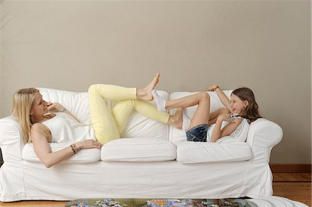 elementary age - Mother and daughter playing footsie on sofa Stock Photo - Premium Royalty-Free, Code: 649-07710795