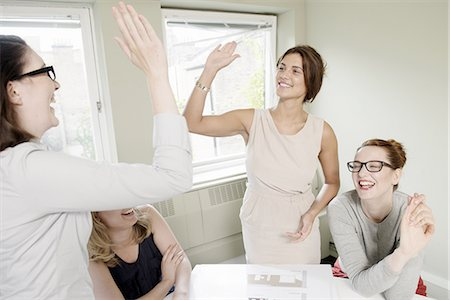 Four businesswomen celebrating with high fives in conference room Stock Photo - Premium Royalty-Free, Code: 649-07736468
