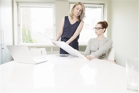 Two businesswoman looking at blueprint design in conference room Stock Photo - Premium Royalty-Free, Code: 649-07736469
