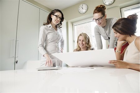 Four female designers looking at blueprint in office Stock Photo - Premium Royalty-Free, Code: 649-07736462
