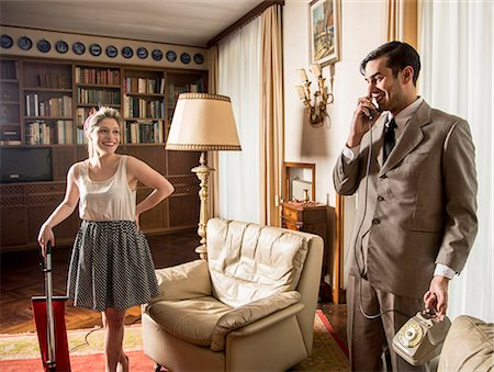 Young vintage couple in sitting room with vintage telephone and vacuum cleaner Stock Photo - Premium Royalty-Free, Code: 649-07736495