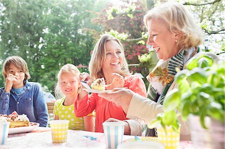Mother serving birthday cake to family at birthday party Stock Photo - Premium Royalty-Free, Code: 649-07736733
