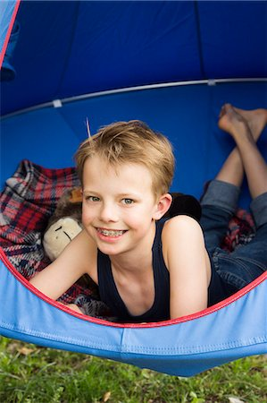 Portrait of smiling boy lying in tent suspended above grass Stock Photo - Premium Royalty-Free, Code: 649-07736779