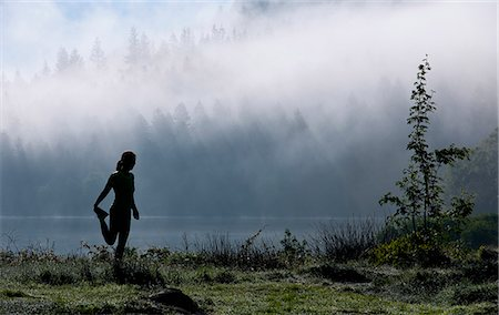 stretching (people exercising) - Female runner stretching by misty lake, Capel Curig, Snowdonia, North Wales, UK Stock Photo - Premium Royalty-Free, Code: 649-07736813