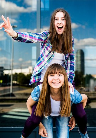Two young women making peace signs and piggybacking Stock Photo - Premium Royalty-Free, Code: 649-07736848