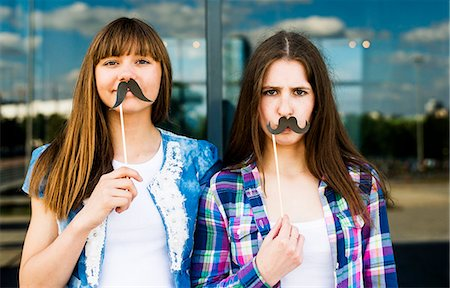 Portrait of two young women holding up mustache costume masks Stock Photo - Premium Royalty-Free, Code: 649-07736855