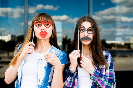 Portrait of two young women holding up lip and eye costume masks Stock Photo - Premium Royalty-Free, Code: 649-07736850