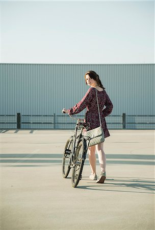 pushing - Young woman looking back whilst pushing bicycle in empty parking lot Stock Photo - Premium Royalty-Free, Code: 649-07736955