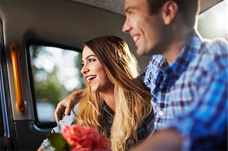 Young woman with boyfriend and bunch of roses in city taxi Stock Photo - Premium Royalty-Free, Code: 649-07737016