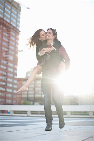 Mid adult man giving girlfriend piggyback on rooftop parking lot Stock Photo - Premium Royalty-Free, Code: 649-07737041