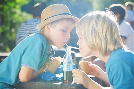 Two young boys drinking from bottle with straws Stock Photo - Premium Royalty-Free, Code: 649-07760860