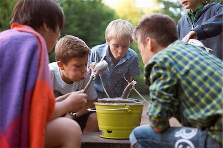 Young boys cooking fish over barbecue Stock Photo - Premium Royalty-Free, Code: 649-07760874