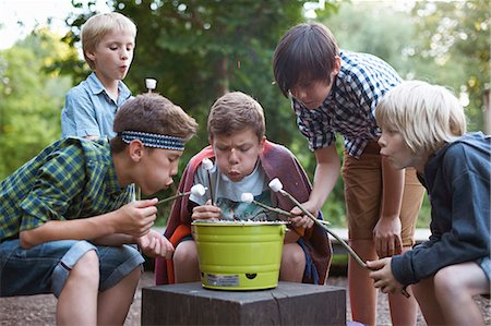 Group of young boys toasting marshmallows over bucket barbecue Stock Photo - Premium Royalty-Free, Code: 649-07760871