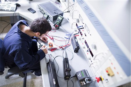 energia - High angle view of male electrician repairing electronic equipment in workshop Fotografie stock - Premium Royalty-Free, Codice: 649-07760895