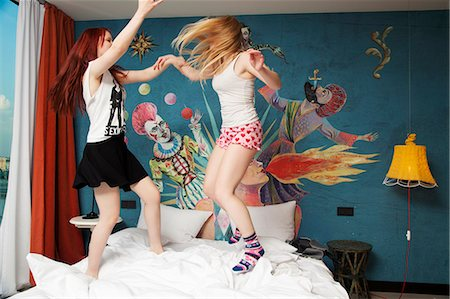 Two young women dancing on hotel bed Stock Photo - Premium Royalty-Free, Code: 649-07760898